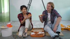 Pares felizes que comem a pizza ao fazer a renovação video estoque