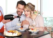 Pares felizes que comemoram com vinho e bolo imagens de stock royalty free