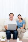 Pares felizes que compram em linha com seu cartão de crédito Fotografia de Stock