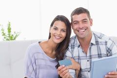 Pares felizes que compram em linha na tabuleta digital usando o cartão de crédito Fotos de Stock Royalty Free