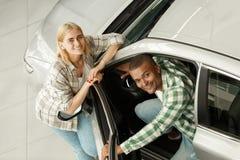 Pares felizes que compram o carro novo junto no negócio imagens de stock royalty free