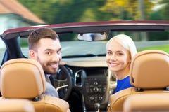 Pares felizes que conduzem no carro do cabriolet sobre a cidade Fotos de Stock Royalty Free
