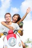 Pares felizes que conduzem o 'trotinette' que tem o divertimento no verão Imagens de Stock