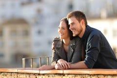 Pares felizes que contemplam vistas de um balcão no por do sol fotografia de stock royalty free