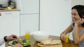 Pares felizes que conversam e que comem o café da manhã junto em casa na cozinha video estoque