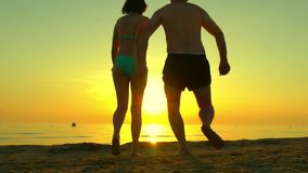Pares felizes que correm ao longo da praia que guarda as mãos em um fundo do por do sol no movimento lento Silhuetas de um par de filme