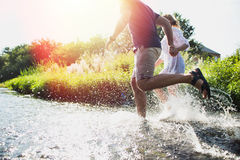 Pares felizes que correm na água pouco profunda Imagens de Stock