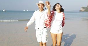 Pares felizes que correm na praia que guarda as mãos homem e mulher felizes novos em turistas do amor em férias vídeos de arquivo