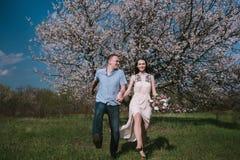 Pares felizes que correm no jardim da flor que guarda em conjunto Imagens de Stock