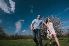 Pares felizes que correm no jardim da flor que guarda em conjunto Imagem de Stock Royalty Free