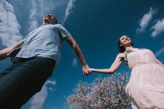 Pares felizes que correm no jardim da flor que guarda em conjunto Foto de Stock Royalty Free