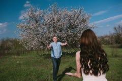 Pares felizes que correm no jardim da flor que guarda em conjunto Imagem de Stock