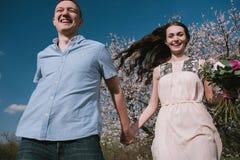Pares felizes que correm no jardim da flor que guarda em conjunto Fotografia de Stock Royalty Free