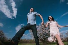 Pares felizes que correm no jardim da flor que guarda em conjunto Foto de Stock