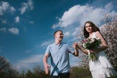 Pares felizes que correm no jardim da flor que guarda em conjunto Fotos de Stock