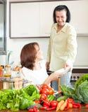 Pares felizes que cortam o aipo para a salada na cozinha home Imagem de Stock Royalty Free