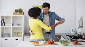 Pares felizes que cozinham o alimento e que dançam em casa filme