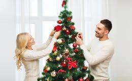 Pares felizes que decoram a árvore de Natal em casa Imagens de Stock