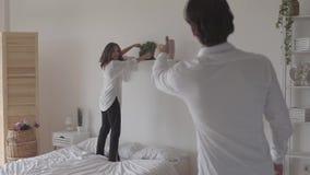 Pares felizes que decoram a sala junto Jovem mulher que põe a pintura mural no meio da prateleira quando seu marido vídeos de arquivo