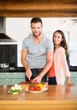 Pares felizes que desbastam vegetais no contador de cozinha imagem de stock royalty free