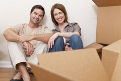 Pares felizes que desembalam as caixas de embalagem que movem a casa Fotografia de Stock Royalty Free