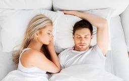 Pares felizes que dormem na cama em casa foto de stock royalty free