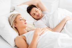 Pares felizes que dormem na cama em casa fotografia de stock