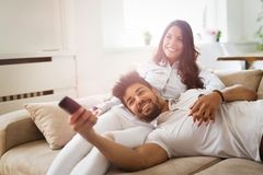 Pares felizes que encontram-se no sofá junto e que relaxam em casa imagem de stock