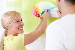 Pares felizes que escolhem cores para pintar imagem de stock royalty free