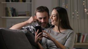 Pares felizes que escutam a música que compartilha de fones de ouvido filme