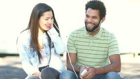 Pares felizes que escutam a música junto, compartilhando de fones de ouvido video estoque