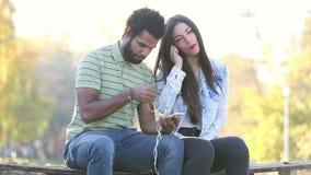 Pares felizes que escutam a música junto, compartilhando de fones de ouvido vídeos de arquivo
