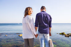 Pares felizes que estão em um cais do mar Pares à moda, guardando a mão, cabelo encaracolado, camisa branca, equipamento causal,  imagem de stock