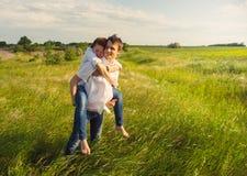 Pares felizes que estão no campo no por do sol Foto de Stock Royalty Free