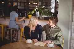 Pares felizes que falam ao sentar-se com copos e menu de café na tabela Imagem de Stock