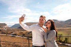 Pares felizes que fazem o selfie contra as montanhas imagem de stock royalty free