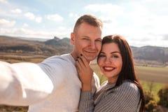 Pares felizes que fazem o selfie contra as montanhas foto de stock