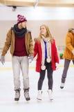 Pares felizes que guardam as mãos na pista de patinagem Imagem de Stock