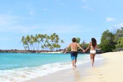 Pares felizes que guardam as mãos na praia das férias do divertimento imagens de stock