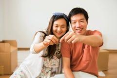 Pares felizes que guardam a chave da casa nova foto de stock royalty free