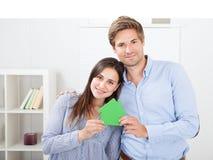 Pares felizes que guardam o modelo da casa verde Fotografia de Stock Royalty Free