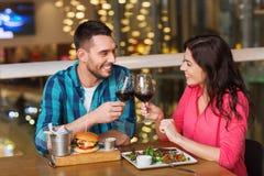 Pares felizes que jantam e vinho da bebida no restaurante foto de stock royalty free