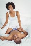 Pares felizes que jogam na cama Imagem de Stock Royalty Free