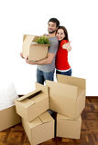 Pares felizes que juntam em uma casa nova que desembala caixas de cartão foto de stock royalty free