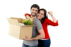Pares felizes que juntam em uma casa nova que desembala caixas de cartão Fotos de Stock Royalty Free