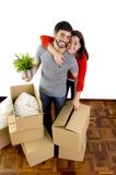 Pares felizes que juntam em uma casa nova que desembala caixas de cartão fotografia de stock