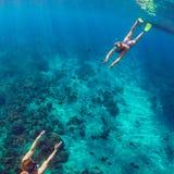 Pares felizes que mergulham debaixo d'água sobre o recife de corais imagem de stock