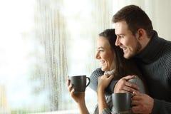 Pares felizes que olham através de uma janela um o dia chuvoso Fotos de Stock Royalty Free