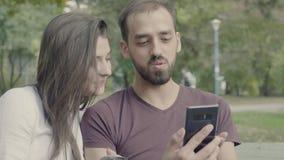 Pares felizes que olham a tela do smartphone filme