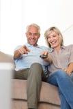 Pares felizes que olham a tevê no sofá Fotografia de Stock